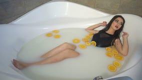 Un castana sexy lussuoso si trova nel bagno con latte e le arance stock footage