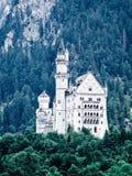 Un castillo Neuschwanstein en montañas de las montan@as. Fotos de archivo libres de regalías