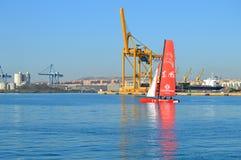 Un catamaran de emballage passe une grue photographie stock libre de droits