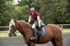 Un cavalier de poney serrant les courroies de périmètre sur une selle photo stock
