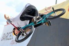 Un cavaliere professionale alla concorrenza di MTB (ciclismo di montagna) sulla pista di sporcizia ai giochi estremi di Barcellon Immagini Stock