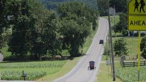 Un cavallo di Amish e una guida con errori lungo la strada sulla campagna video d archivio
