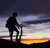 Un cazador con los ciervos en la puesta del sol Foto de archivo