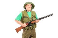 Un cazador masculino maduro que sostiene un rifle Foto de archivo libre de regalías
