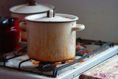 Un cazo sucio en una cocina-gama sucia Imágenes de archivo libres de regalías