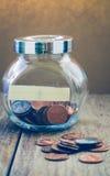 Un centavo acuña en el bolso de cristal del tarro y del yute Imagen de archivo