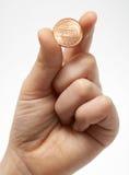 Un centavo en una mano Imagen de archivo libre de regalías