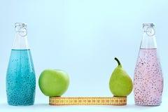 Un centimetro, una mela, le bottiglie di vetro e del pera con il seme del basilico del rosa e del supporto blu di colore su un fo fotografia stock libera da diritti