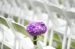 Un centro de flores al lado de sillas en una boda Fotos de archivo