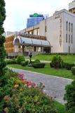 Un centro di affari moderno con il territorio adiacente ben curato sui precedenti di alta costruzione di vetro Immagine Stock Libera da Diritti