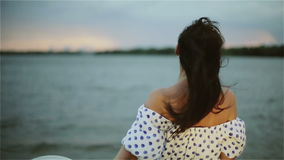 Un centro envejeció a la mujer que ponía de su sombrero en la playa en la puesta del sol almacen de video