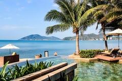 Un centro turístico tropical con la opinión de la piscina y del mar Foto de archivo