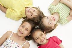 Un cerchio di quattro giovani amici che si trovano giù sorridendo Fotografia Stock Libera da Diritti