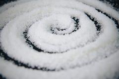 Un cerchio di zucchero granulared su fondo nero Fotografie Stock