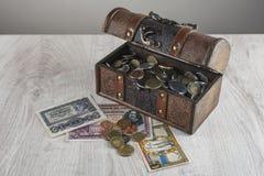 Un cercueil, un coffre au trésor avec des pièces de monnaie et vieux billets de banque, découvertes rares Le concept des aventuri Images libres de droits