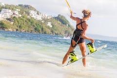 Un cerf--surfer de jeune femme prêt pour des tours surfants de cerf-volant dans s bleu Photos stock