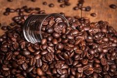 Un certo chicco di caffè in vetro del mucchio del chicco di caffè sulla tavola di legno Fotografia Stock