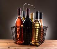 Un cestino della spesa del cavo riempito di bottiglie di vino Fotografia Stock Libera da Diritti