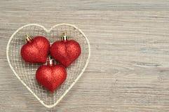 Un cesto metallico ha riempito di bagattelle rosse di forma del cuore Immagini Stock