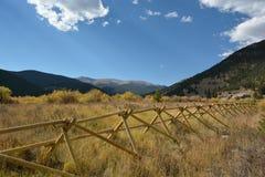 Un champ dans les montagnes avec des cieux bleus et une barrière en bois Image stock