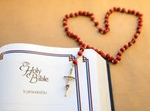 Un chapelet en bois sous forme de coeur sur la bible et l'endroit FO photographie stock
