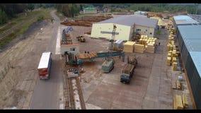 Un chariot monte dans la campagne près d'une usine de travail du bois banque de vidéos