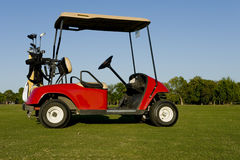 Un chariot ou une poussette de golf rouge Image stock