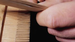 Un charpentier principal rectifie un peigne en bois manuellement avec la fin de ponçage de papier  4 K clips vidéos
