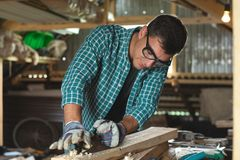 Un charpentier surface la machine de rabotage en bois de main dans l'atelier à la maison photographie stock