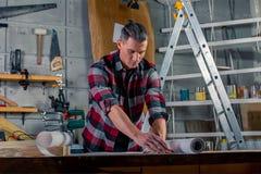 Un charpentier travaille Charpentier étudiant le projet de dessin Dans la perspective de l'atelier photographie stock