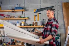 Un charpentier travaille Charpentier étudiant le projet de dessin Dans la perspective de l'atelier photo stock