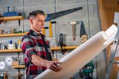 Un charpentier travaille Charpentier étudiant le projet de dessin Dans la perspective de l'atelier images libres de droits