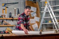Un charpentier travaille Charpentier étudiant le projet de dessin Dans la perspective de l'atelier image libre de droits
