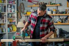 Un charpentier travaille au travail du bois la machine-outil Scie des détails de meubles avec une scie circulaire Processus de sc image libre de droits