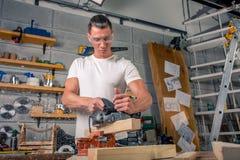 Un charpentier travaille au travail du bois la machine-outil Scie des détails de meubles avec une scie circulaire Processus de sc photos libres de droits