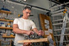 Un charpentier travaille au travail du bois la machine-outil Scie des détails de meubles avec une scie circulaire Processus de sc photo libre de droits