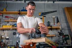 Un charpentier travaille au travail du bois la machine-outil Scie des détails de meubles avec une scie circulaire Processus de sc photographie stock