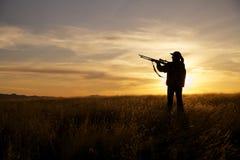 Chasseur féminin de fusil dans le coucher du soleil Photographie stock