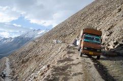 Un chauffeur de camion de marchandises manoeuvrant son véhicule par une route étroite de montagne Photo libre de droits