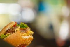 Un cheeseburger degli alimenti a rapida preparazione con un morso preso da un morso preso da  immagini stock
