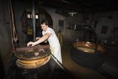 Un cheesemonger in una latteria antica, Franche-Comté, Francia Immagini Stock