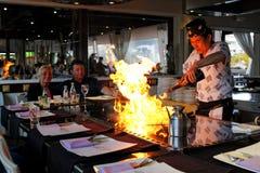 Un chef de teppanyaki faisant cuire à un teppan alimenté au gaz Images stock