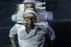Un chef masculin posant avec l'eau du fond de couteau du ` s de cuisinier Photographie stock