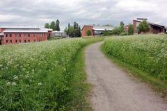 Un chemin dans le pré avec des maisons dans la distance images stock
