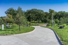 Un chemin en parc soigné moderne avec des arbres verts et un pont en bois image stock