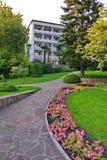 Un chemin en pierre avec les fleurs plantées, les arbres verts grands et une pelouse mène à un bâtiment blanc de cinq-histoire av image stock