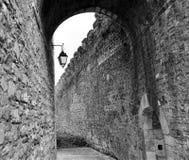 Un chemin entre les murs du château et une lampe Images stock