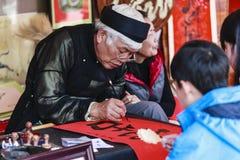 Un chercheur écrit les caractères chinois de calligraphie au temple de la littérature Photographie stock libre de droits
