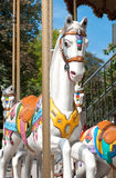 Un cheval blanc caracole sur le carrousel photographie stock