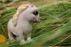 Un cheval de jouet dans l'herbe Image libre de droits